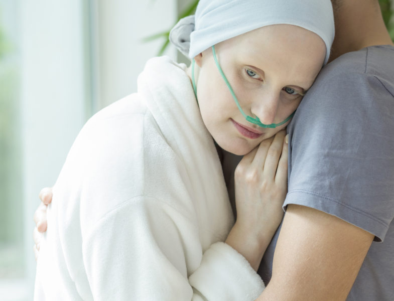 Weak woman with cancer hugging her husband during chemotherapy